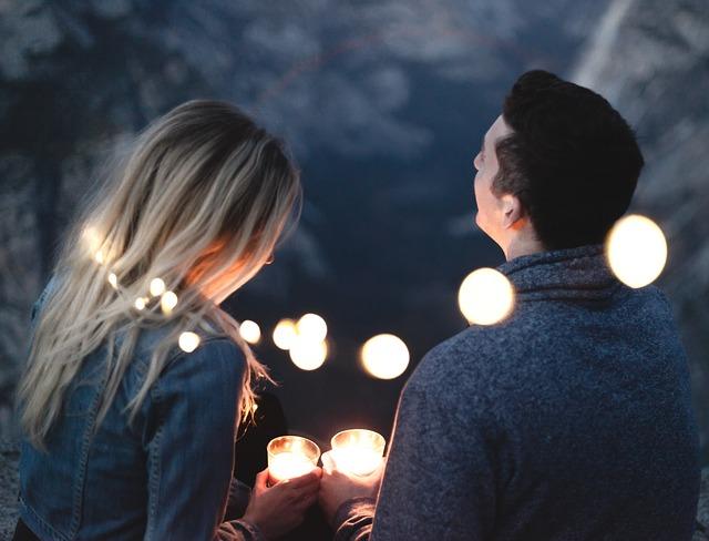 Muž a žena v sivom oblečení sedia na terase veľa svietiacich lampiónov