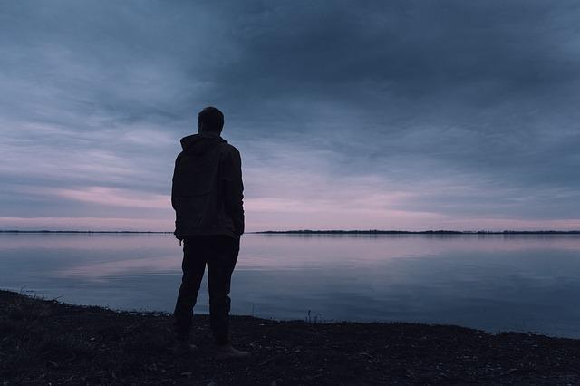 Muž v bunde stojí pri jazere počas súmraku