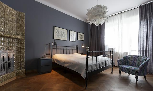 Spálňa s veľkou posteľou, nábytkom a bielym lustrom.jpg